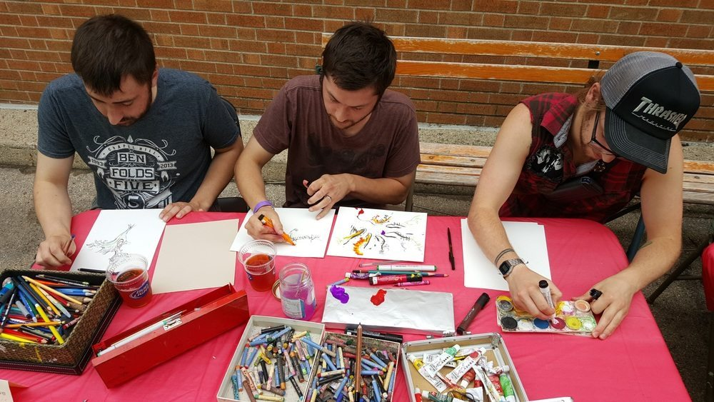 Luke Crowe draws witha couple of friends who spontaneously joined in the effort at the Drawing Rally.